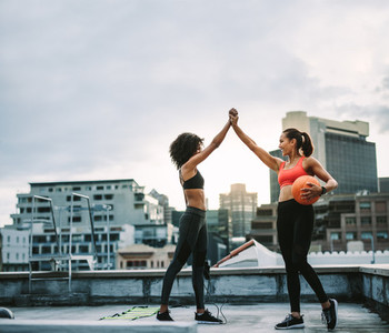 Fitness women giving high five during workout on rooftop
