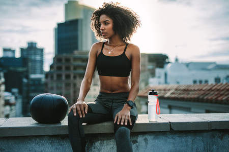 Fitness woman sitting on rooftop relaxing