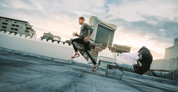 Athlete training on rooftop running with a resistance parachute