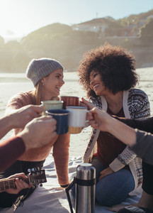 Friends toasting coffee cups at the beach