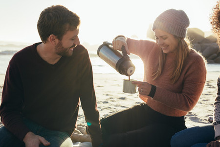 Smiling friends having coffee at the beach