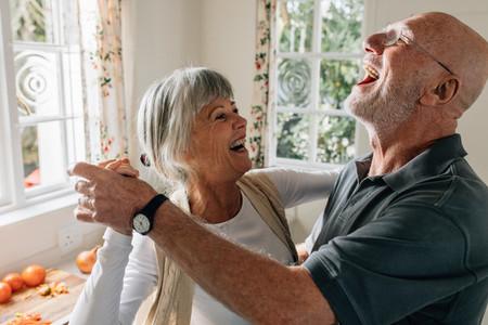 Senior couple laughing and having fun dancing