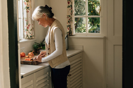 Senior woman preparing food in kitchen