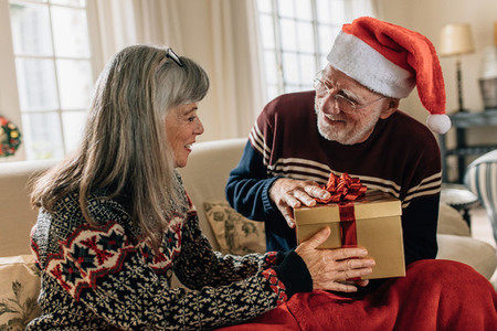 Senior couple at home exchanging christmas gifts
