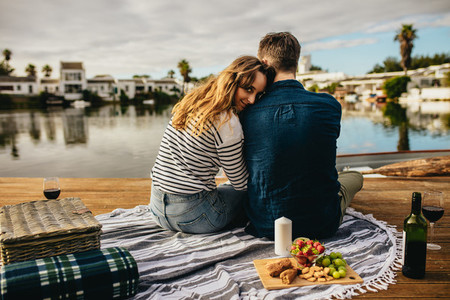 Romantic couple on a date sitting near a lake with snacks
