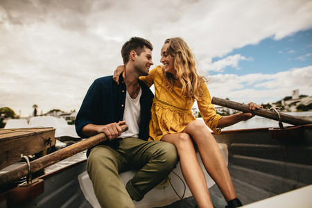 Man and woman sitting in a boat looking at each other