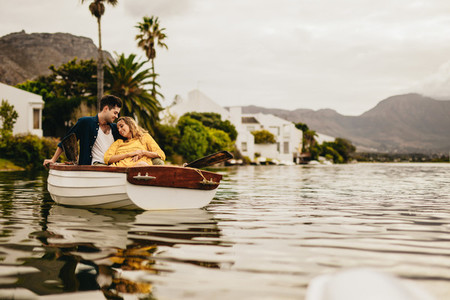 Couple sitting together in a boat relaxing on a date