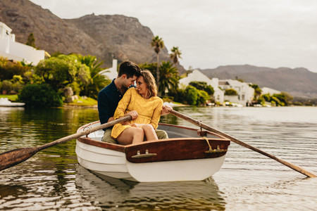 Couple having fun sitting in a boat on a date