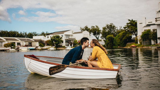 Romantic couple sitting in a boat and kissing