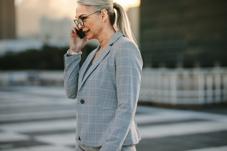 Mature businesswoman on way to home using phone