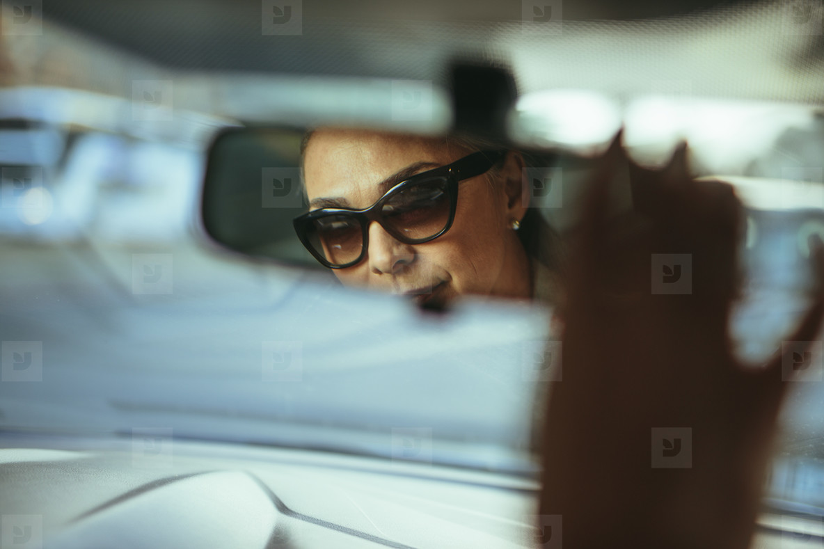 Senior woman driver adjusting rear view car mirror