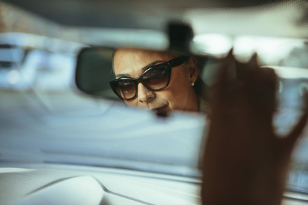 Senior woman driver adjusting rear view car mirror
