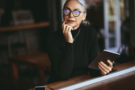 Senior businesswoman at coffee table with digital tablet