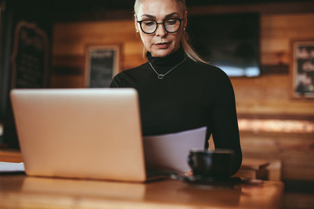 Senior businesswoman reviewing few documents at cafe