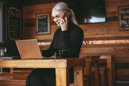Businesswoman at cafe making a phone call and using laptop