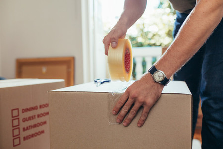 Close up of a man applying adhesive tape on a packing box