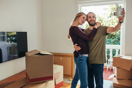 Couple posing for selfie in their new apartment