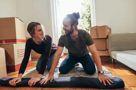 Happy couple rolling a carpet together at home