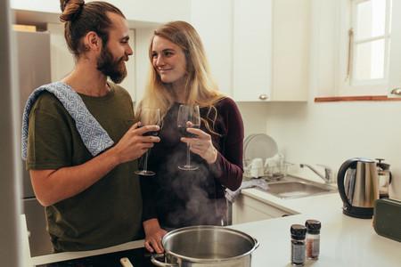Happy couple at home enjoying wine