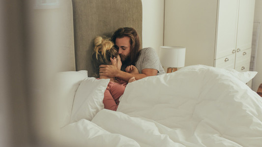 Couple sleeping on bed under a cozy blanket