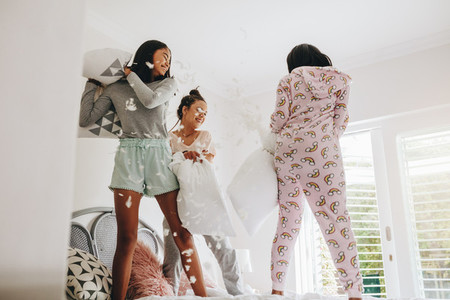 Girls pillow fighting standing on bed