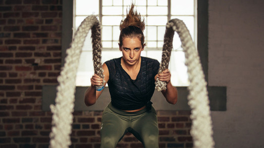 Sportswoman exercising with battling ropes at gym