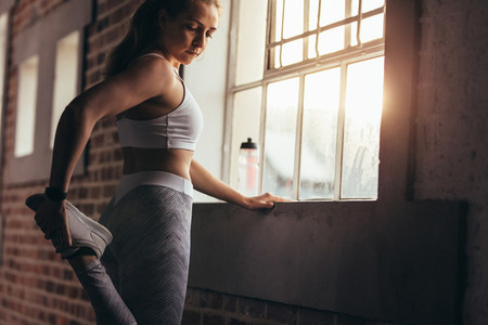 Healthy woman doing warmups at gym