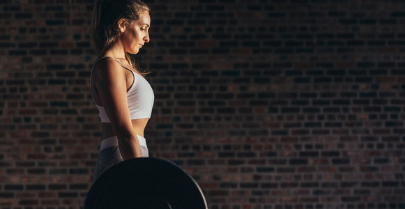 Strong woman lifting heavy weights at gym