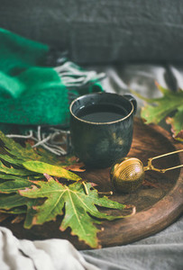 Mug of tea with sieve and colofrul fallen autumn leaves