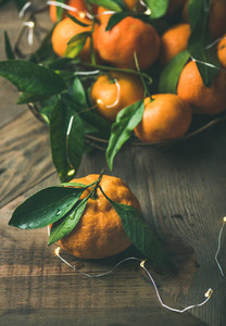 Fresh tangerines with leaves and light garland