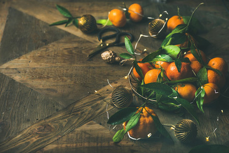 Fresh tangerines with leaves and decoration toys over rustic table