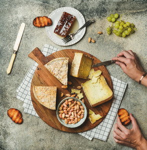 Cheese platter with female hands reaching to food flat lay