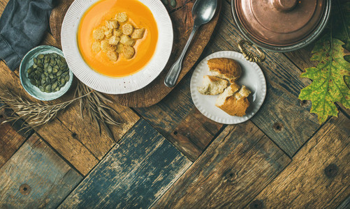 Fall pumpkin cream soup with croutons and seeds  flat lay