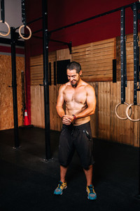 Athletic young smiling man prepares to do some cross fit exercises without a shirt