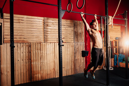 Athletic young man doing pull ups exercises without t shirt in a crossfit gym