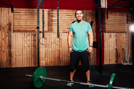 Athletic young smiling man prepares to do some weightlifting exercises with green t shirt