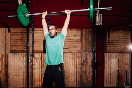 Athletic young man doing some weightlifting exercises with green t shirt