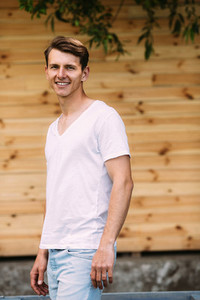 handsome guy on the background of wooden wall