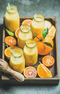 Healthy yellow smoothie in bottles in wooden tray