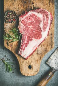 Raw beef steak rib eye on board with seasoning top view