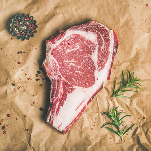 Raw steak rib eye with seasoning on craft paper square crop