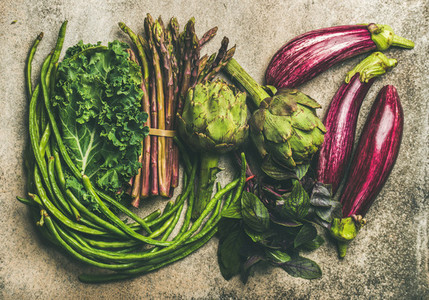 Flat lay of fresh green and purple vegetables over concrete background