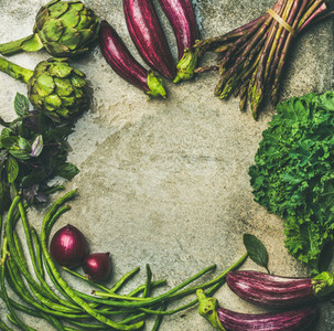 Flat lay of green and purple raw vegetables over grey background