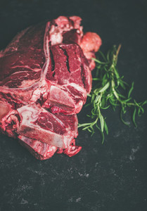 Raw beef meat t bone steaks with rosemary copy space