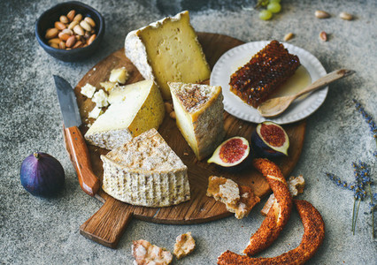 Cheese assortment figs honey freshly baked bread and nuts