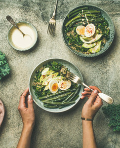 Quinoa  kale  green beans  avocado  egg bowls in female hands