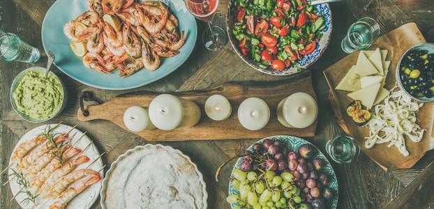 Flat lay of salad  shrimps  olive  grape  cake  wide composition