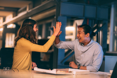 Cheerful business partners giving high five at office