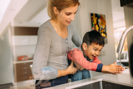 Mother helping son to wash hands after baking