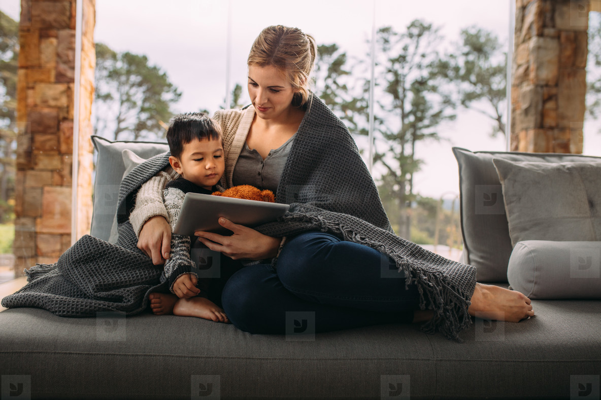 Mother and son with digital tablet in the living room